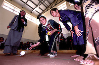 ..KABUL 24 August 2005..Female athlete wearing a white scarf, throwing a red ball, plays bocce's game at Bagh-e-Zanana...On 23-25 August 2005, Special Olympics Afghanistan held its first national Games at Olympic Stadium in Kabul. More than 300 athletes, including 80 female athletes, experienced a taste of happiness and achievement for the first time in their lives. They competed in athletics, bocce and football (soccer). Because of cultural restrictions, males and females competed at separate venues.