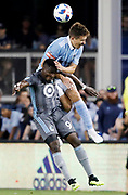 Sporting Kansas City defender Matt Besler, top, heads the ball over Minnesota United defender Abu Danladi, bottom, during the second half of a MLS soccer match in Kansas City, Kan., Saturday, Aug. 25, 2018. Sporting KC beat United 2-0. (AP Photo/Colin E. Braley)