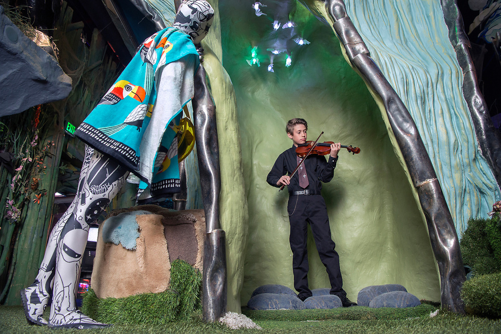 em053117g/jnorth/Stephanie Kitts, left, peeks in as Weston Keller, 12, from Santa Fe, plays violin as part of Meow Wolf's Summer in the Multiverse at the House of Eternal Return in Santa Fe Wednesday May 31, 2017.  (Eddie Moore/Albuquerque Journal