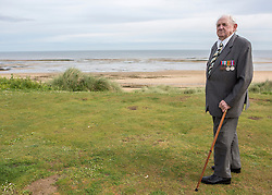 """© Licensed to London News Pictures. 29/05/2014. Dennis takes a moment to reflect as he stands on Sword Beach. """"I stood there and watched the shell fly over my head.  It missed me by inches.  It was like everything was in slow motion. """" Photo credit : Alison Baskerville/LNP"""