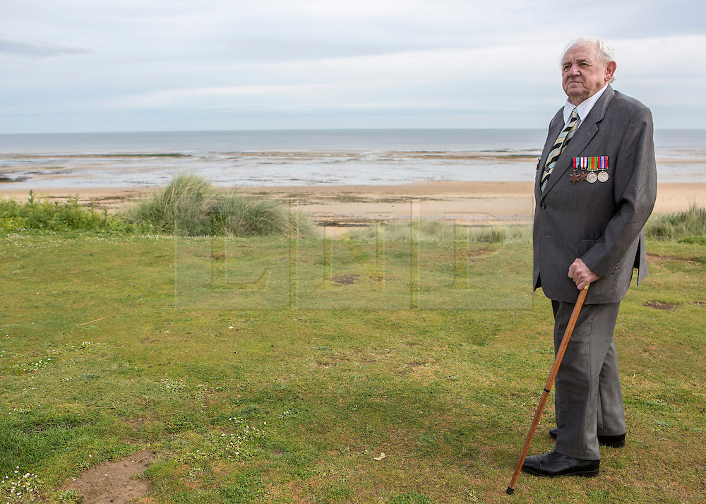 "© Licensed to London News Pictures. 29/05/2014. Dennis takes a moment to reflect as he stands on Sword Beach. ""I stood there and watched the shell fly over my head.  It missed me by inches.  It was like everything was in slow motion. "" Photo credit : Alison Baskerville/LNP"