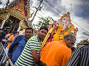 "15 SEPTEMBER 2013 - BANGKOK, THAILAND: Hindus in Bangkok carry statues of Ganesha to a waiting boat for the immersion on the last day of Ganesha Chaturthi celebrations at Shiva Temple in Bangkok. Ganesha Chaturthi is the Hindu festival celebrated on the day of the re-birth of Lord Ganesha, the son of Shiva and Parvati. The festival, also known as Ganeshotsav (""Festival of Ganesha"") is observed in the Hindu calendar month of Bhaadrapada. The festival lasts for 10 days, ending on Anant Chaturdashi. Ganesha is a widely worshipped Hindu deity and is revered by many Thai Buddhists. Ganesha is widely revered as the remover of obstacles, the patron of arts and sciences and the deva of intellect and wisdom. The last day of the festival is marked by the immersion of the deity, which symbolizes the cycle of creation and dissolution in nature.  In Bangkok, the deity (statue) was submerged in the Chao Phraya River.         PHOTO BY JACK KURTZ"