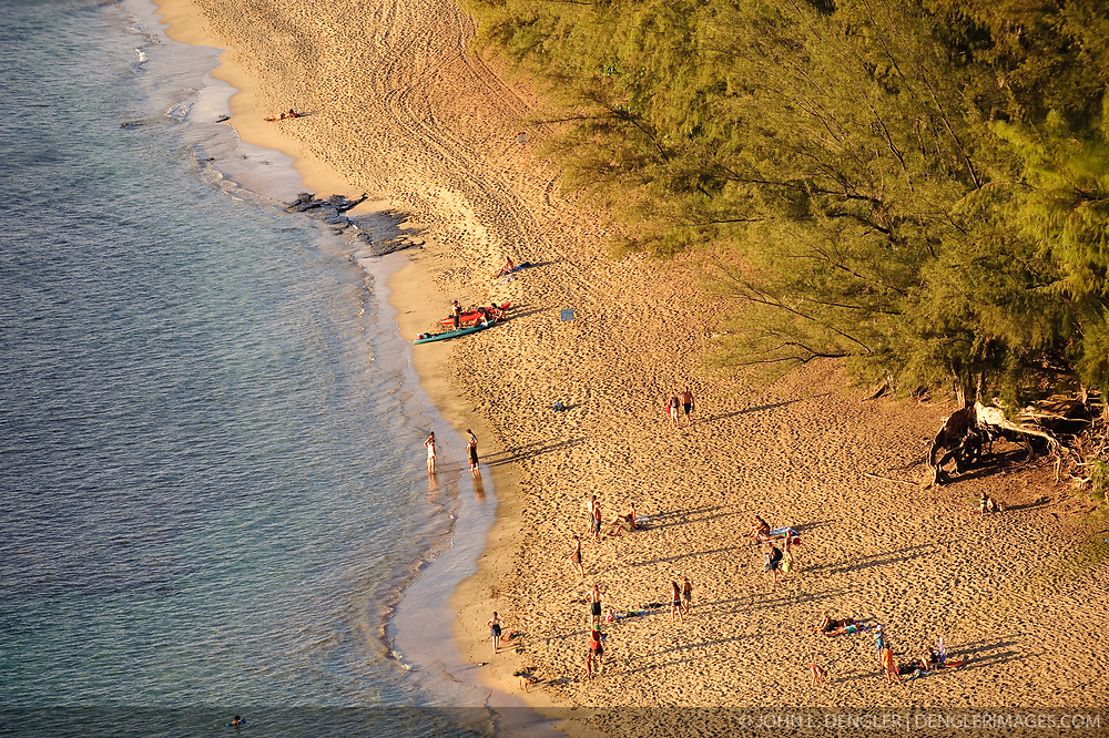 Late afternoon sunlight shines on Kee Beach in Haena State Park on north shore of the island of Kauai in Hawaii. The beach, noted for its snorkeling and being the end of the road on the north shore is located next to the trailhead for the Kalalau Trail which runs along the rugged Na Pali coast. The photo is taken from the Kalalau Trail.