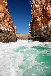 Wildwater rushes through the smaller of the two gaps at the Horiztonal Waterfalls, Talbot Bay on the Kimberley coast, on an outgoing tide.