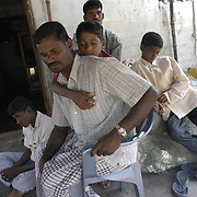 Chinayyan Apparasu, center, a fisherman, sits with his four children and his brother, rear, Pulaventhiran, also a fisherman, and his remaining fishing nets at his home in Perumalpettai, a fishing village in Tamil Nadu, India, on January 15, 2005, after the area was struck by the Indian Ocean Tsunami on December 26, 2004, killing 37 of the villagers and destroying nearly all of their fishing equipment. Generated by an earthquake on the ocean floor, the tsunami devastated the fishing industry along the southeastern coast of India.