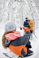 A mid adult woman and man pose while a young woman takes their picture while snowshoeing through a snow covered forest in Bend, Oregon. (releasecode: jk_mr1033, jk_mr1035, jk_mr1034) (Model Released)