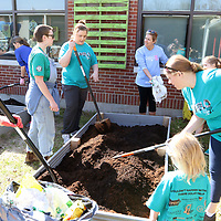 Volunteers from ECEC and the Renasant group help fill up boxes of mulch for the garden at ECEC Saturday for the 10 for Tupelo clean up