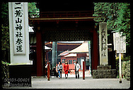 Two women and man exit the main gate of Futaara-san Shrine on an October afternoon in Nikko. Japan