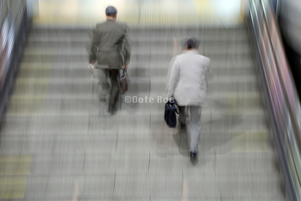 two businessmen running up the stairs