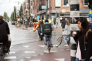 Uber Eats backpack food delivery cyclist in Amsterdam at the crossing Overtoom direction Bilderdijk straat