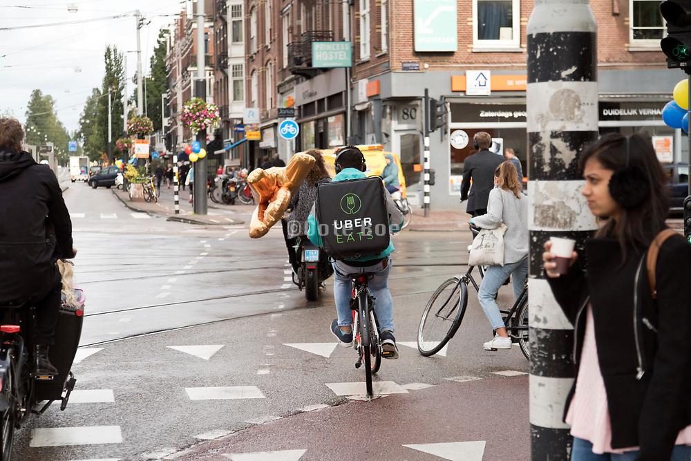 Uber Eats backpack food delivery cyclist in Amsterdam at the crossing Overtoom direction Bilderdijk straat