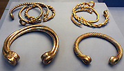 Bottom left Electrum torc from Snettisham (Hoard G) Iron Age, around 75 BC. From Ken Hill, Snettisham, Norfolk, England, part of hoard G found at Snettisham, which was buried in a small pit cut into the rock. It contained 3 torcs made of electrum (a naturally occurring alloy of gold and silver), 7 silver torcs and 10 bronze torcs. Top left and bottom right:Gold torcs from the Ipswich HoardIron Age, around 75 BC. Found near Ipswich, Suffolk, England. Five of these gold torcs were found during construction work near Ipswich in 1968