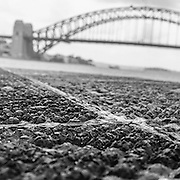 Old manhole cover (detail) with Harbour Bridge in the background, Sydney, Australia