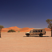 Lone safari vehicle in Namibia Sossusvlei dunes.