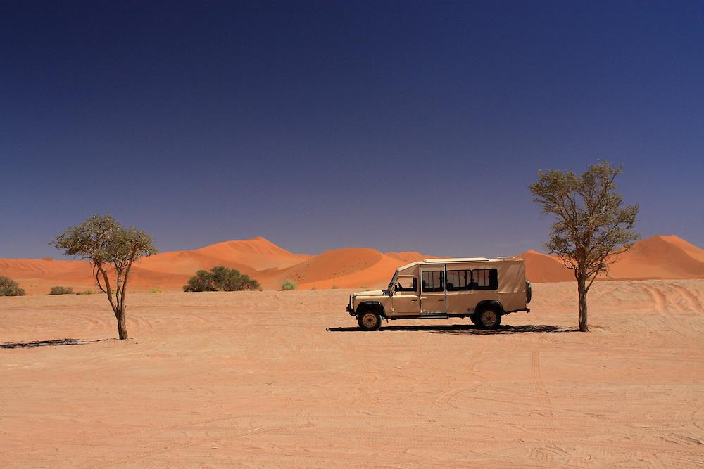Lone safari vehicle in Namibia Sossusvlei dunes.
