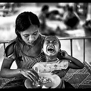 A young Burmese mother, an ethnic Karen, attend to her sick child at the Mae Tao clinic in Mae Sot, Thailand.  (Photo by David Longstreath)