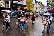 In Utrecht lopen drie stelletjes onder paraplu's door de binnenstad.<br /> <br /> In Utrecht three couples are walking under umbrellas in the shopping center.