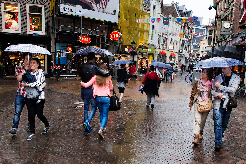 In Utrecht lopen drie stelletjes onder paraplu's door de binnenstad.<br /> <br /> In Utrecht three couples are walking under umbrellas in the shopping center.