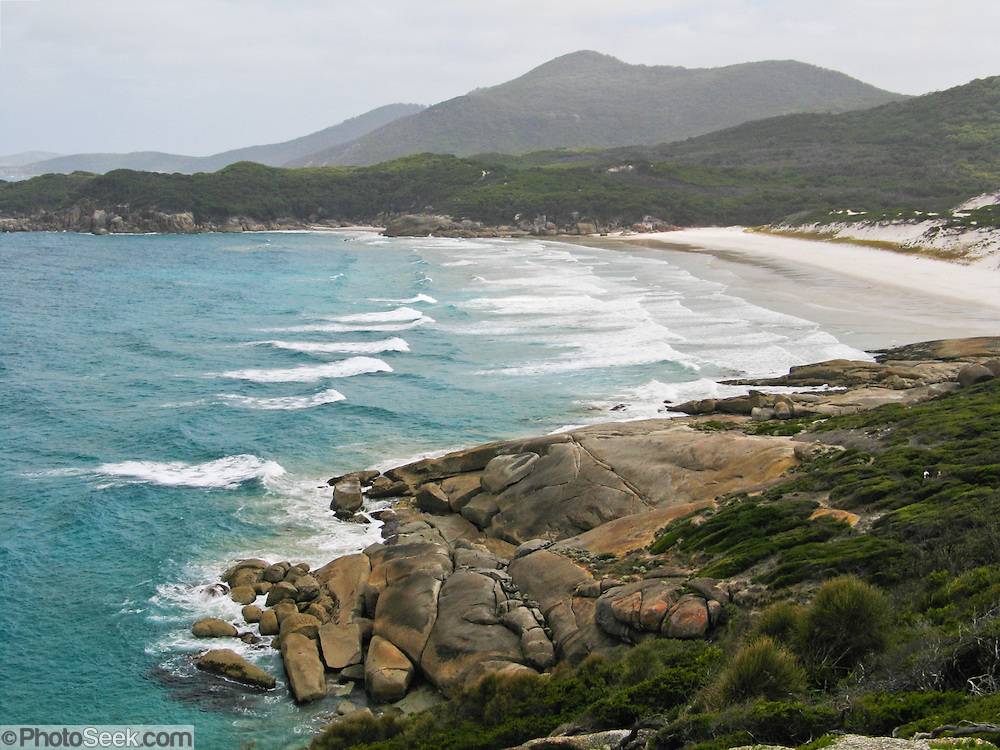 """Indian Ocean (or Southern Ocean according to Australian geographers) waves wash onto a fine white sand beach at Wilson's Promontory National Park in the Gippsland region of Victoria, Australia. Drive two hours from Melbourne to reach Wilson's Promontory, or """"the Prom,"""" which offers natural estuaries, cool fern gullies, magnificent and secluded beaches, striking rock formations, and abundant wildlife."""