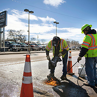 City of Gallup Street Department workers Elliot Tsosie, left, and Nathan Young patch potholes with a premix asphalt at Aztec and 5th street in downtown Gallup, Wednesday, Feb. 27.
