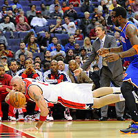 23 November 2013:   Washington Wizards center Marcin Gortat (4) dives for a loose ball and manages to keep in in bounds against New York Knicks power forward Amar'e Stoudemire (1) as the Washington Wizards defeated the New York Knicks, 98-89 at the Verizon Center in Washington, D.C.