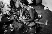 Poona Bai, a '1984 Gas Survivor',  40, is holding her son Raj, 7, a boy affected by a severe neurological disorder, while making Indian chai tea for her family in Oriya Basti, one of the water-affected colonies near Bhopal, Madhya Pradesh, central India, near the abandoned Union Carbide (now DOW Chemical) industrial complex.