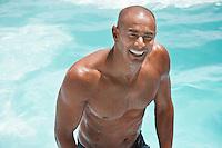 Man in swimming pool smiling half length