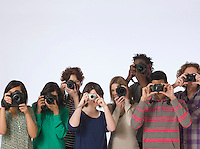 Group of young people making photo straight at camera studio shot