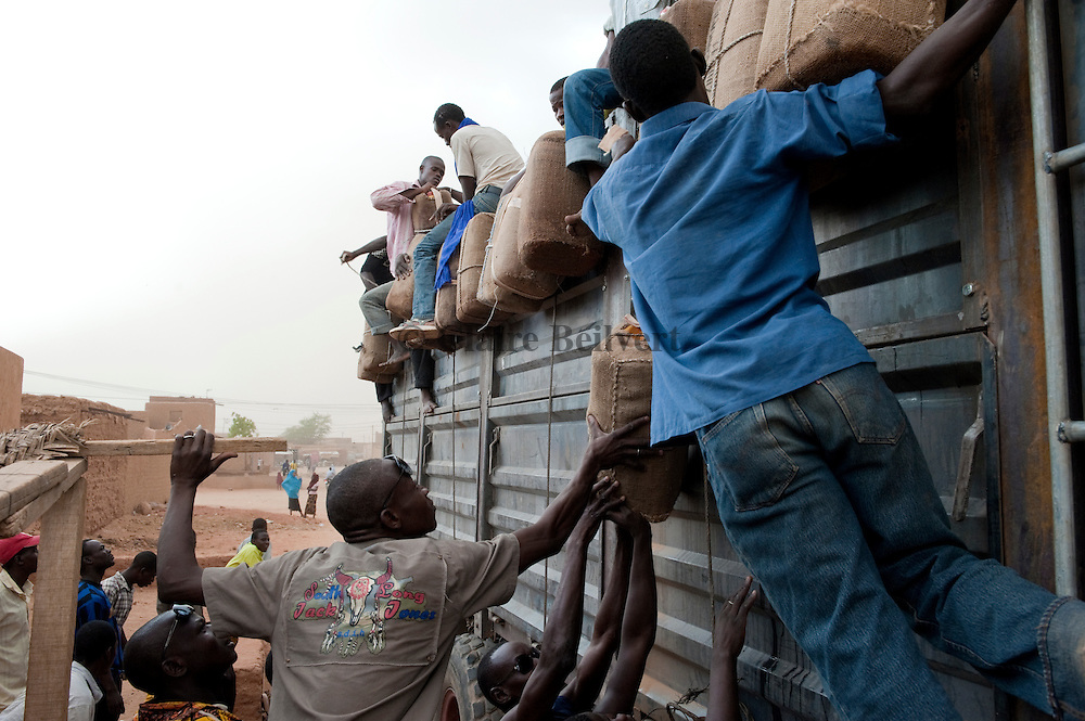 In front of their ghetto in Agadez. Young african migrants on a truck preparing their travel to Dirkou. They hang some cans full with water for their travel through the ténéré desert