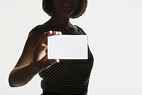 Smiling silhouetted woman standing holding large blank card mid section