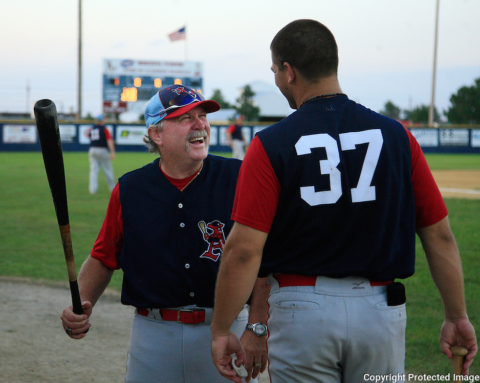 Clarinda A's coach Craig Hindman has a friendly chat with pitcher Stuart Smith during the team's game with the Omaha Diamond Spirit.  photo by David Peterson