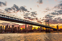 Manhattan Bridge at sunset (Brooklyn Bridge and Lower Manhattan skyline in background), New York, New York USA.