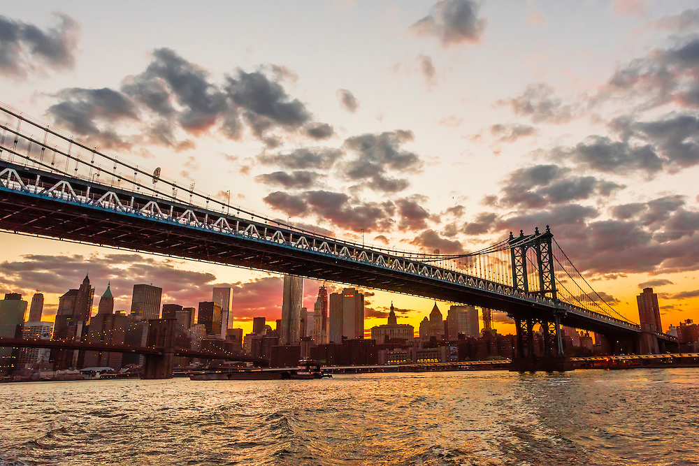 Manhattan Bridge at sunset (Brooklyn Bridge and Lower Manhattan skyline in background), New York, New York USA.
