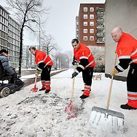 Nederland, Amsterdam , 8 januari 2010..Een team van de Amsterdamse Gemeente reiniging schept sneeuw en ijs weg op voetpaden zoals hier bij het Flevohuis aan de Zeeburgerdijk. bejaardentehuizen en andere plekken.Foto:Jean-Pierre Jans