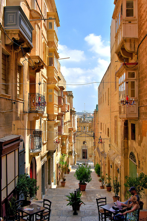Couple Eating on St. Lucia Street in Valletta, Malta<br /> Many of Malta&rsquo;s towns have narrow and winding streets flanked by connected buildings. This layout was important for defense but also provides a breeze and a shadowed respite from the summer heat. However, when Valletta was planned in the 16th century, it followed a rectangular grid with wider roads. You can still find narrow terraced streets like St. Lucia that offer a romantic spot to take a break. One word of caution when navigating the city&rsquo;s steps: the risers are taller than normal because they were designed to accommodate knights in heavy armor. In the background is St. Lucy, a Roman Catholic church built in 1570.