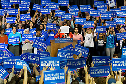 A member of Bernie Sanders' campaign staff holds up a white piece of paper for videographers to test white balance as the crowd goes wild thinking the rally is set to begin.
