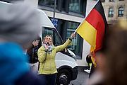 Frankfurt am Main   11 Apr 2015<br /> <br /> Am Samstag (11.04.2015) demonstrierten etwa 35 Personen der Gruppe &quot;Freie B&uuml;rger f&uuml;r Deutschland&quot; (FBfD, ex PEGIDA) auf dem Rossmarkt in Frankfurt am Main gegen &quot;Islamisierung&quot;, ihre Redebeitr&auml;ge gingen in dem Geschrei der etwa 800 Gegendemonstranten unter.<br /> Hier: FBfD-Aktivisten singen das Deutschlandlied, Heidi Mund schwenkt die Deutschlandfahne.<br /> <br /> &copy;peter-juelich.com<br /> <br /> [Foto honorarpflichtig   No Model Release   No Property Release]