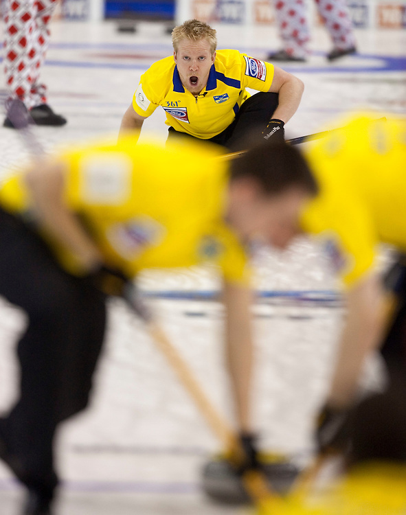 Swedish skip Niklas Edin yells encouragement his sweepers during the bronze medal match against Norway at the Ford World Men's Curling Championships in Regina, Saskatchewan, April 10, 2011.<br /> AFP PHOTO/Geoff Robins