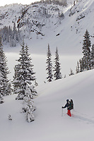A skiier skies down toward Twin Outlets Lake in deep powder snow.  Beartooth Mountains, Montana.