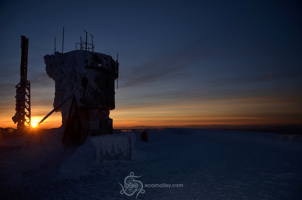 The sun sets behind the Mount Washington Observatory tower.