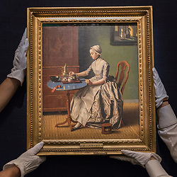 "© Licensed to London News Pictures. 01/07/2016. London, UK.  Technicians prepare to hang ""A Dutch Girl at Breakfast"" by Jean-Etienne Liotard (est. GBP 4-6 million), at the preview of Sotheby's London Old Masters evening sale which takes place 6 July.   Photo credit : Stephen Chung/LNP"