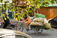 Woman transporting bags of garbage on a three wheeled bike.