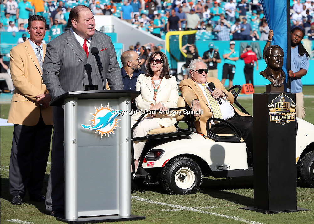 Pro Football Hall of Fame president David Baker speaks at the podium at a halftime event intended to honor former Miami Dolphins head coach Don Shula (seated) during the Miami Dolphins 2015 week 11 regular season NFL football game against the Dallas Cowboys on Sunday, Nov. 22, 2015 in Miami Gardens, Fla. The Cowboys won the game 24-14. (©Paul Anthony Spinelli)