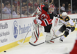 Apr 10; Newark, NJ, USA; New Jersey Devils goalie Johan Hedberg (1) plays the puck away from Boston Bruins center Tyler Seguin (19) during the first period of their game at the Prudential Center.