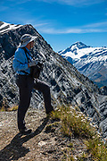 A hiker views Mount Aspiring / Tititea (3033 m or 9951 ft, New Zealand's 23rd-highest mountain) from Cascade Saddle. In 5 days, we tramped the strenuous Rees-Dart Track for 39 miles plus 20km side trip to spectacular Cascade Saddle, in Mount Aspiring National Park, Otago region, South Island of New Zealand.