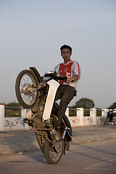 A young vietnamese man proudly makes some wheeling with his motorbike. Hanoi, Vietnam, Asia