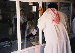 Pakistan, Karachi, 2004. A man waits for test results outside an Edhi Center family planning clinic.
