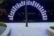 "The three letter IATA codes for some of the world's airport destinations have been used as part of an art design in a plaza outside Heathrow Airport's Terminal 5. An arc of these neon-lit codes form an arch on a panel near one of the 1,500 semi mature trees. Illuminated in a sequence, they are all lit here before the sequence re-starts and they all become dimmed. Terminal 5 was created by the Richard Rogers Partnership (now Rogers Stirk Harbour and Partners) and has the capacity to serve around 30 million passengers a year. From writer Alain de Botton's book project ""A Week at the Airport: A Heathrow Diary"" (2009)."