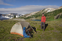 Adult male in red shirt standing by tent at backcountry camp, Tapto Lakes. North Cascades National Park, Washington
