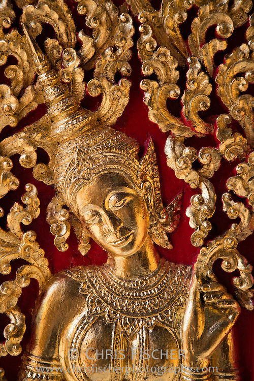 Details from a golden wood carved panel on the doors to the royal funeral carriage house (Hohng Kep Mien) at Wat Xieng Thong, Luang Prabang, Laos.
